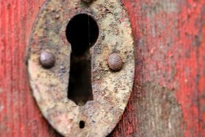 Close up detail of rusty and decaying old door keyhole in timber door with peeling red paint