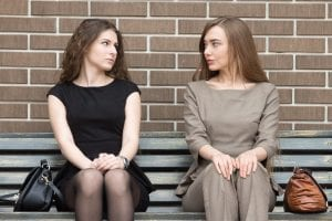 Portrait of two beautiful young female rivals sitting side by side on bench and looking at each other with challenging expressions. Attractive caucasian office women ready for confrontation