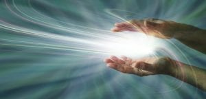 Parallel female hands with a swirling light burst between on a blue energy field background