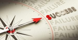Compass pointing the word success made in magnetic material over old fashioned paper concept for motivation purpose